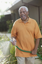 Older men watering plants in backyard - CAIF00740