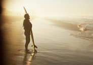 Surfer standing with board on beach - CAIF00860