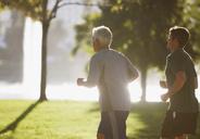 Older men jogging together in park - CAIF00863