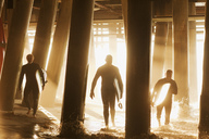 Surfers carrying boards under pier - CAIF00869