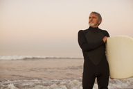 Older surfer carrying board on beach - CAIF00872