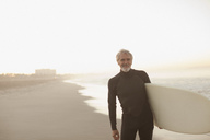 Older surfer carrying board on beach - CAIF00875
