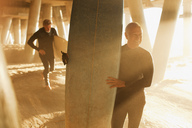 Older surfers carrying boards under pier - CAIF00878