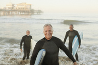 Older surfers carrying boards on beach - CAIF00884