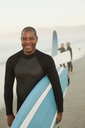 Older surfer carrying board on beach - CAIF00890