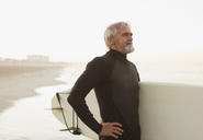 Older surfer carrying board on beach - CAIF00893