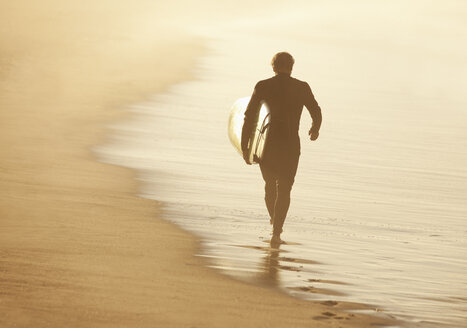 Older surfer carrying board on beach - CAIF00896