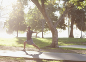Man practicing yoga in park - CAIF00899