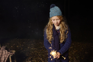 Girl playing with sparkler outdoors - CAIF00902