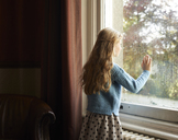 Girl looking out window - CAIF00929