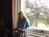 Girl reading by window - CAIF00938