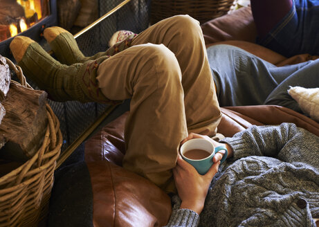 Boy drinking cup of coffee by fire - CAIF00947