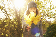Girl holding autumn leaf outdoors - CAIF00953