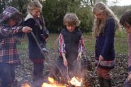 Children poking bonfire outdoors - CAIF00956