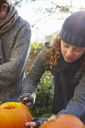 Children carving pumpkins together outdoors - CAIF00968