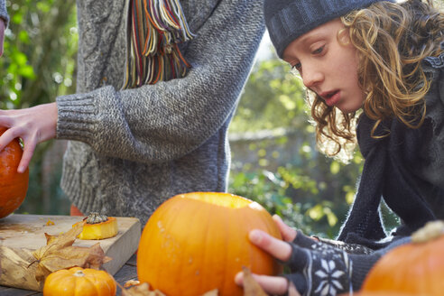 Children carving pumpkins together outdoors - CAIF00974