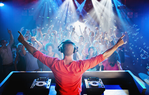 DJ with arms outstretched overlooking dance floor - CAIF01046