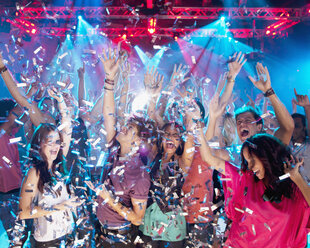 Confetti falling over enthusiastic crowd on dance floor of nightclub - CAIF01049