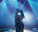 Couple dancing and kissing under spotlights on empty dance floor of nightclub - CAIF01052