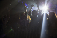 Spotlight above silhouette of crowd cheering at concert - CAIF01076