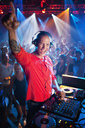 Portrait of enthusiastic DJ at turntable in nightclub - CAIF01082