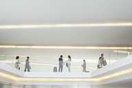 Business people on elevated walkway in airport - CAIF01124