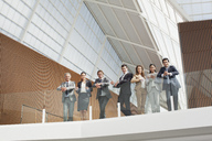 Portrait of smiling business people leaning on balcony railing - CAIF01130
