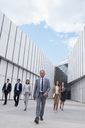 Confident business people walking outside building - CAIF01139