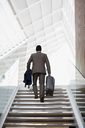 Businessman with suitcase ascending stairs - CAIF01145