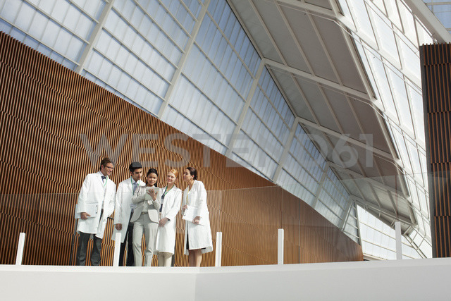 Doctors and businesswoman using digital tablet on modern balcony - CAIF01151