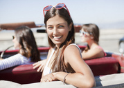 Smiling woman sitting in convertible - CAIF01163