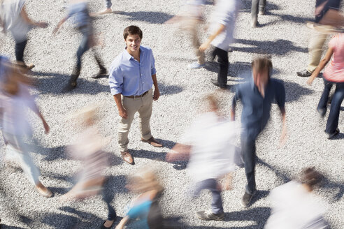 Portrait of smiling businessman surrounded by people rushing by - CAIF01166
