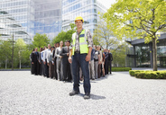 Portrait of smiling construction worker with business people in background - CAIF01184
