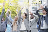 Crowd of business people cheering with arms raised - CAIF01190