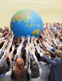 Crowd of business people reaching for globe - CAIF01223