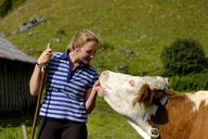 Germany, Bavaria, smiling young woman with cow in the mountains - LBF01811