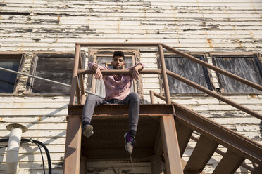 Portrait of stylish young man sitting on staircase outdoors - SUF00465