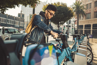 Stylish young man on the street with rental bike - SUF00471