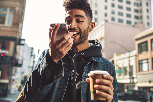 Portrait of stylish young man with coffee and smartphone on the street - SUF00474