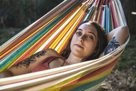 Portrait of young woman with tattoo lying in hammock - SUF00483
