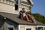 Happy friends sitting on roof - SUF00486