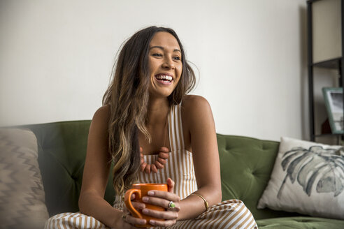 Laughing young woman with coffee mug sitting on couch - SUF00489