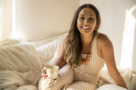 Portrait of happy young woman with coffee cup in bed - SUF00495