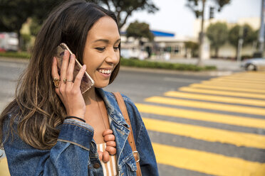 Smiling young woman talking on smartphone on the street - SUF00498