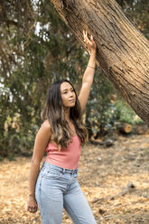 Young woman leaning against tree trunk - SUF00504