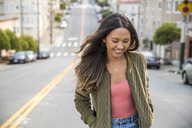Portrait of laughing young woman on the street - SUF00507
