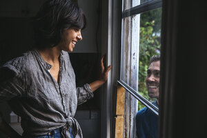 Happy couple smiling at each other through the window - SUF00513