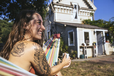Happy young woman with tattoo in hammock - SUF00522
