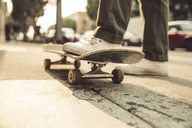 Close-up of man with skateboard on sidewalk - SUF00528