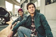 Two smiling young men sitting on sidewalk - SUF00531